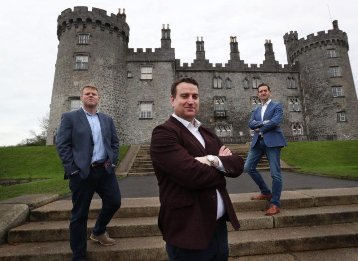 Three men are standing socially distanced outside a castle.