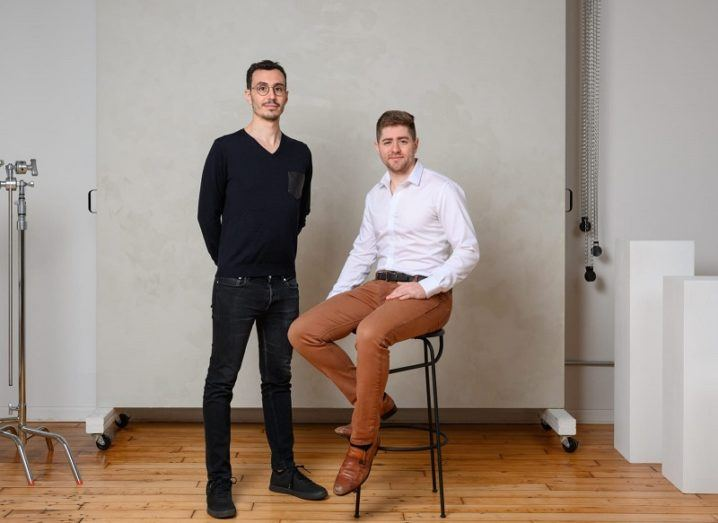 Two men are in a studio. One is standing and one is sitting on a stool.