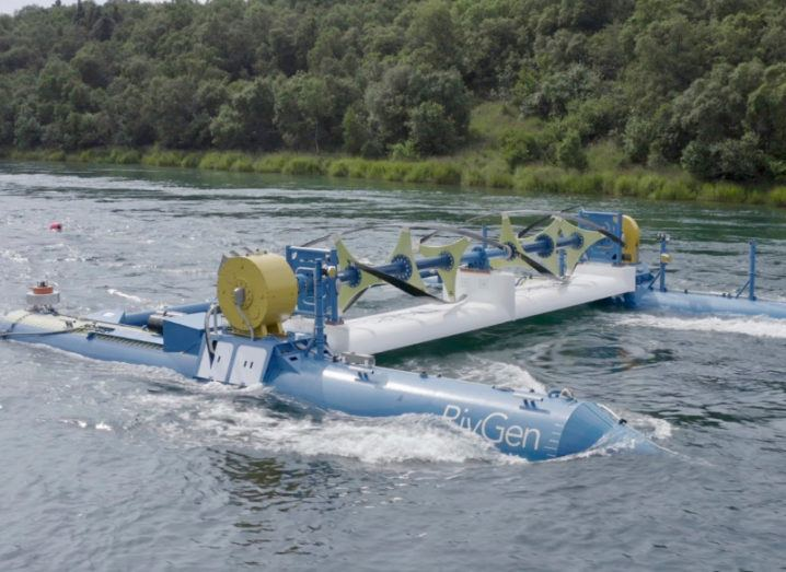 A large blue and white marine turbine in a river with green trees in the background.