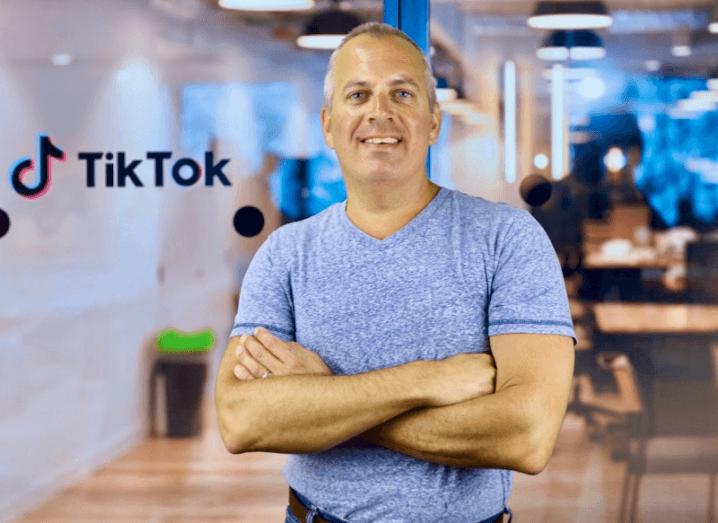 Roland Cloutier, global CSO of TikTok, stands in front of a glass office in a blue t-shirt smiling at the camera.