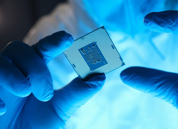 A close-up of gloved hands holding a semiconductor, representing the global chip shortage.