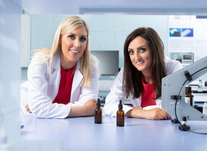 Two women wearing white lab coats are leaning on a countertop in a lab setting.