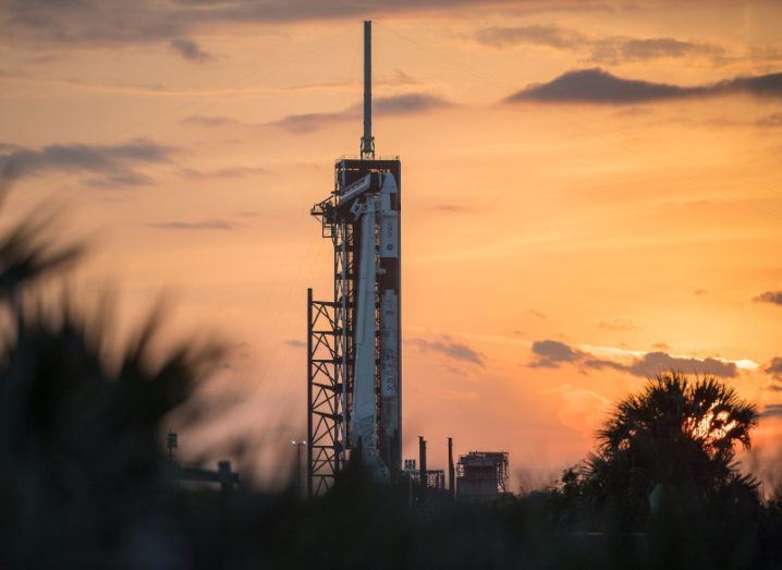 A large Space X Falcon 9 rocket sitting against an orange sky at sunset ahead of the NASA launch.