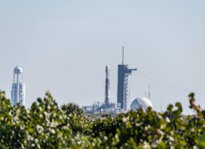 SpaceX Falcon 9 Starlink L-17 sitting on launch pad at Kennedy Space Center over a row of hedges on a bright day.