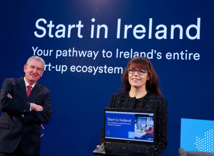 A man and a woman stand in front of a screen that says 'Start in Ireland'. The woman is holding a laptop, with the Start in Ireland portal open on the screen.