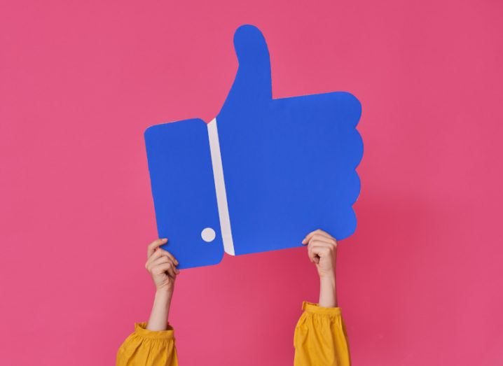 Hands are holding up a large cutout of a thumbs-up emoji, resembling the Facebook 'like' icon.