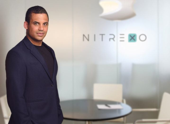 A man stands in an office in front of a sign that says Nitrexo.