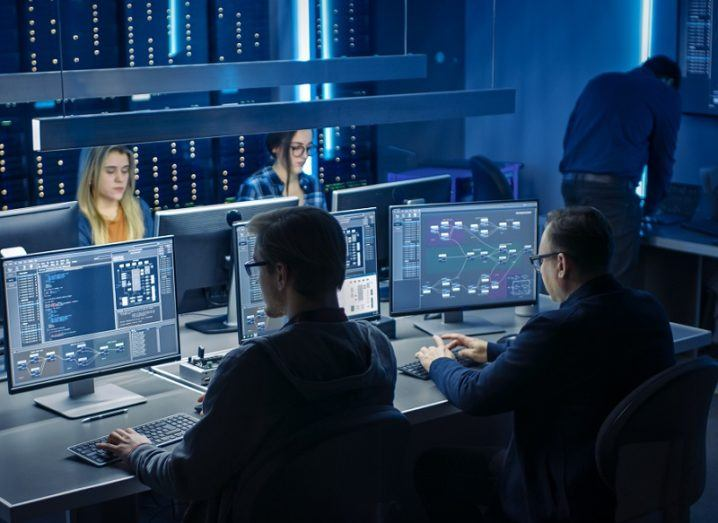 A team is working on computers in a darkened room.