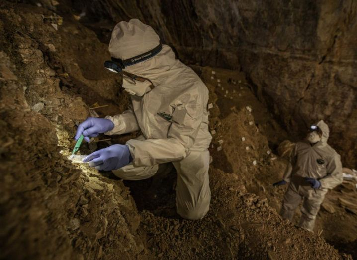 Two researchers in protective gear are taking sediment samples for DNA sequencing in a cave.