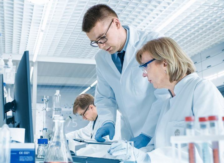 Three scientists in white lab coats are doing studies in a lab setting.