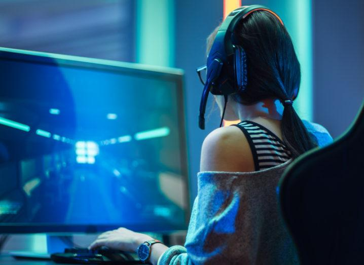 A girl sits in a gaming chair at a large computer screen wearing headphones in a darkened room playing video games.