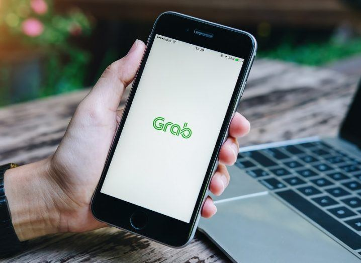 A person's hand is holding a phone with the Grab app open on the screen.
