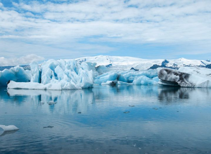 Glaciers melting in a blue ocean against a bright blue sky with clouds, showing the climate crisis.