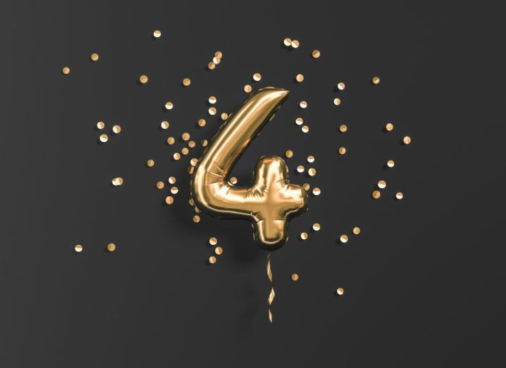 A gold foil balloon in the shape of the number four surrounded by gold confetti against a black background.