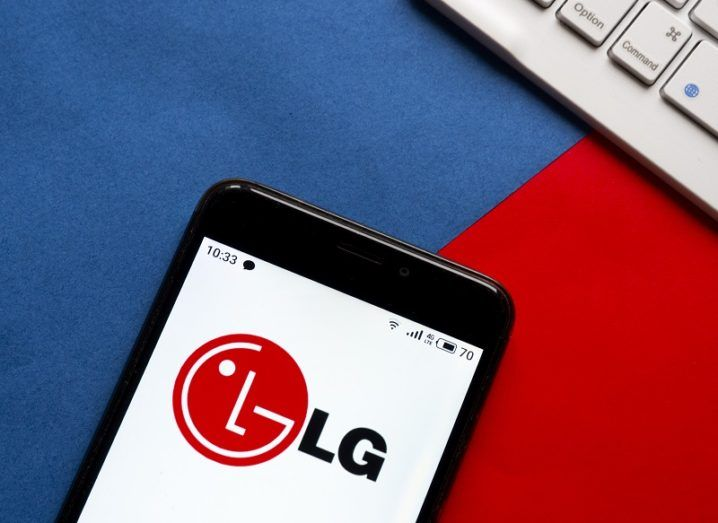 A smartphone is sitting on a desk, with the LG logo on the screen.