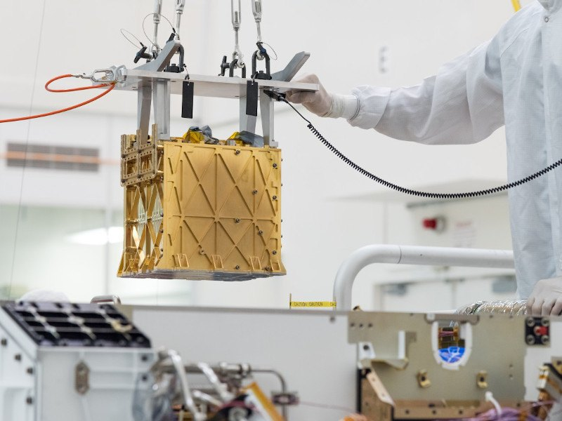 A small gold box is being lowered into a NASA rover in a lab setting.