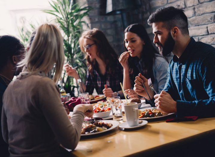 Group of happy business people eating together in restaurant.