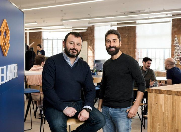 TrueLayer's two co-founders stand in an open office space.