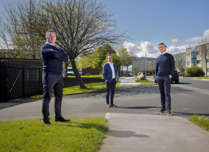 Three men are standing outside under a blue sky in a business park, with offices behind them.