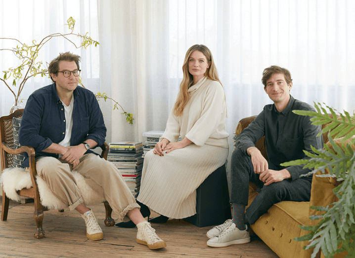 Jonathan Legge, Ciara Flood, Mark Legge sit together in a living room space with a white curtain behind them.