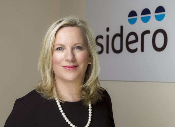 A headshot of Carmel Owens smiling in front of a sign that has the Sidero logo on it.