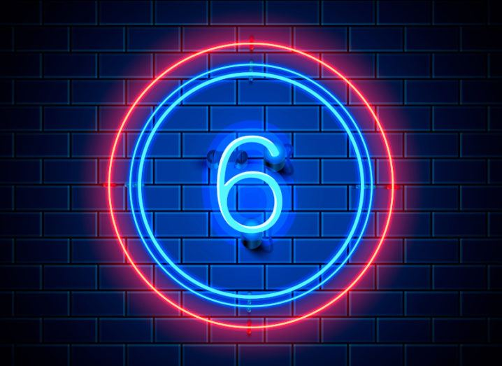 A neon blue number six with a red and blue circle around it against a dark brick wall.
