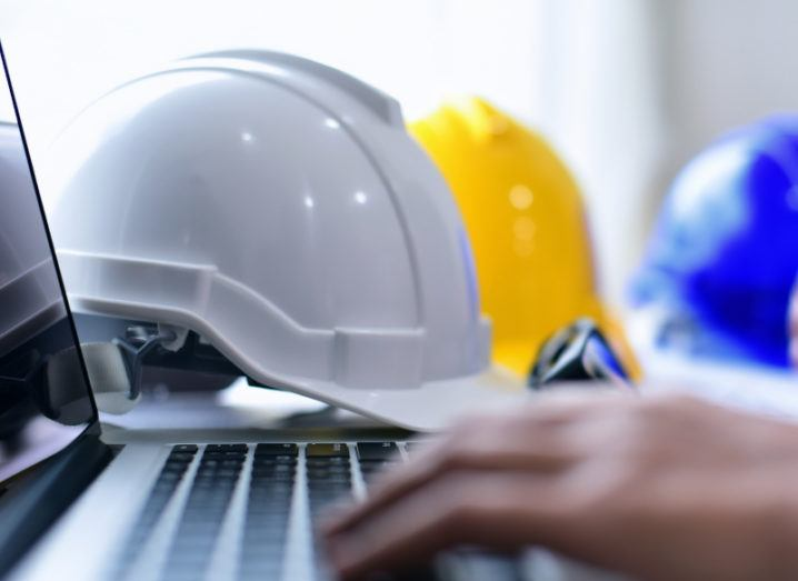 Hands typing on a laptop keyboard. A number of colourful hard hats are visible in the background.