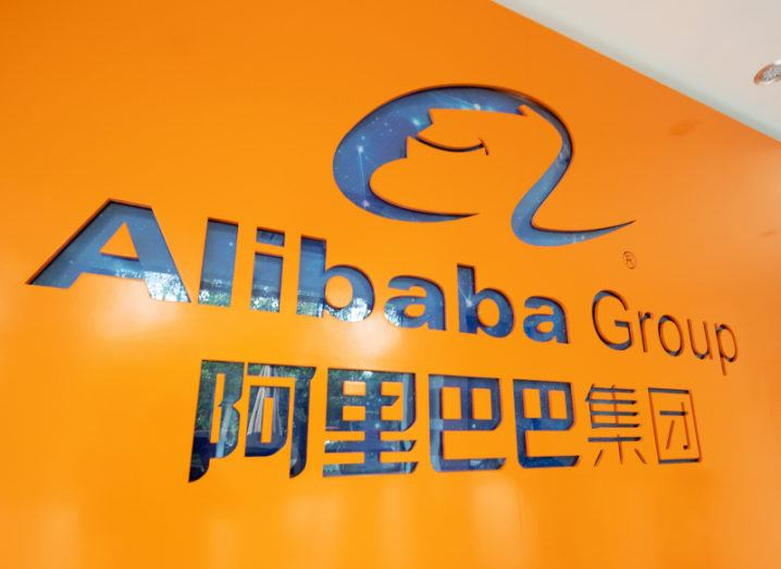 An orange wall inside an office emblazoned with the Alibaba Group logo.