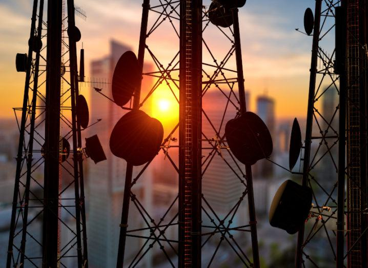 Telecom towers with antennas in silhouette against a sunset.