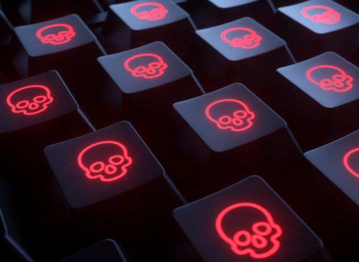 Close-up of a computer keyboard where all keys bear a glowing red skull, indicating a cyberattack.