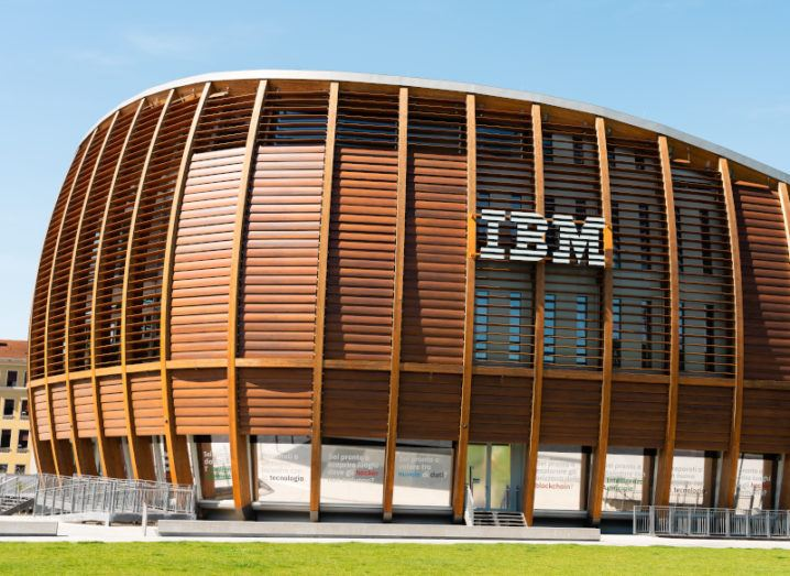 A large wooden building with the IBM logo on the side is shown under a bright blue sky.
