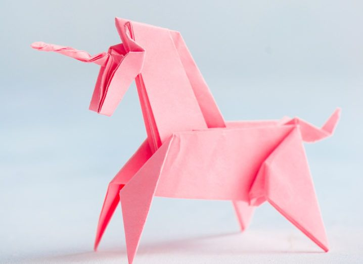 A pink origami unicorn against a blue background.