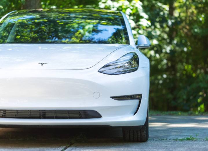 A white Tesla Model 3 electric car parked in front of trees.