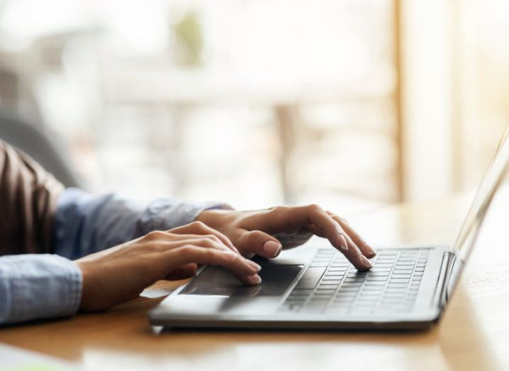 A woman's hands are typing on a laptop.