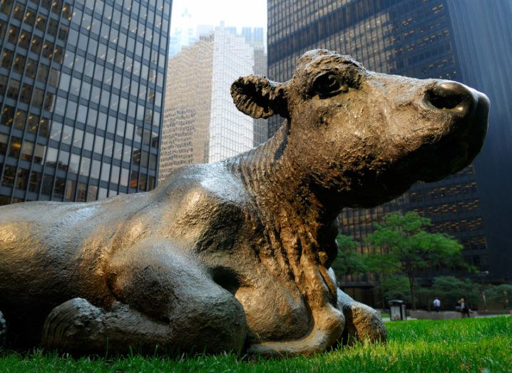 A bronze cow statue lays on grass among large tower buildings in downtown Toronto.