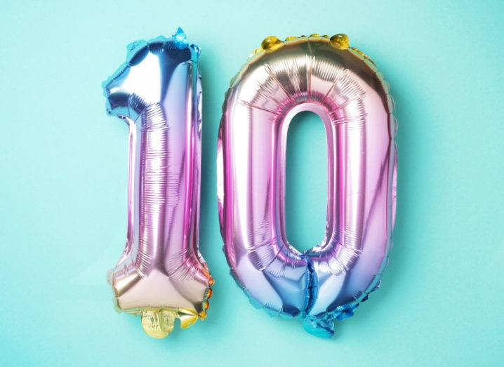 Colourful holographic balloons shaped like the number 10 against a pale blue background.