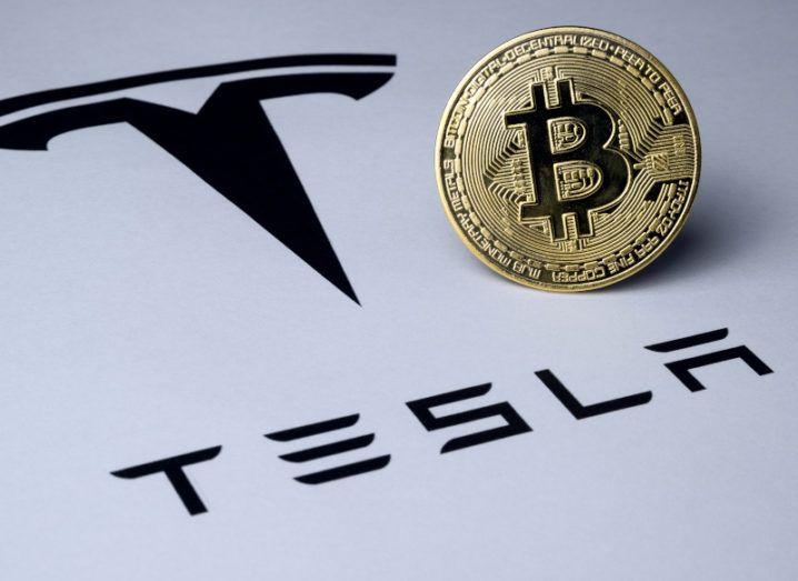 A golden coin bearing the bitcoin logo stands alongside a sheet bearing the Tesla logo.
