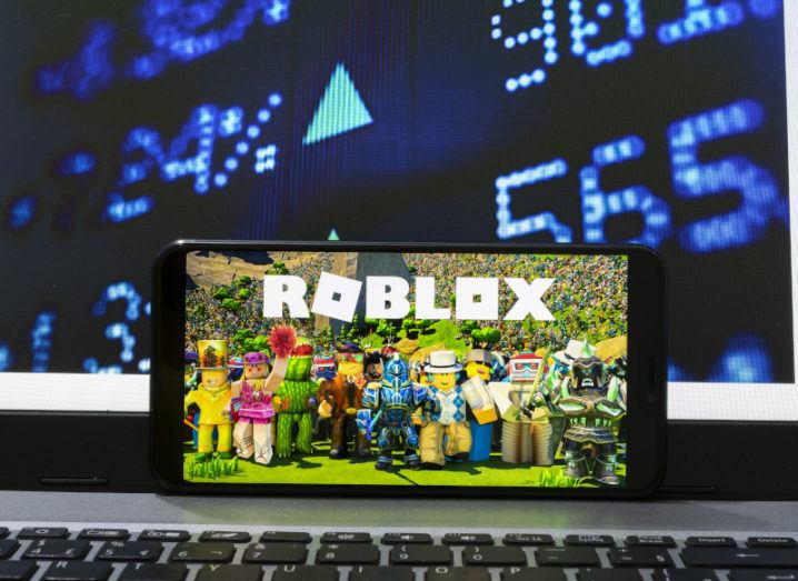A smartphone displaying an opening screen for the Roblox platform rests on an open laptop showing live stock market prices.