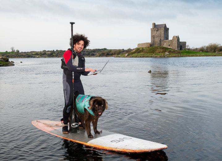 Ian Walsh with Mena from Wet Mongrel Adventures booking his place online while paddle-boarding near Dunguaire Castle, Co Galway.