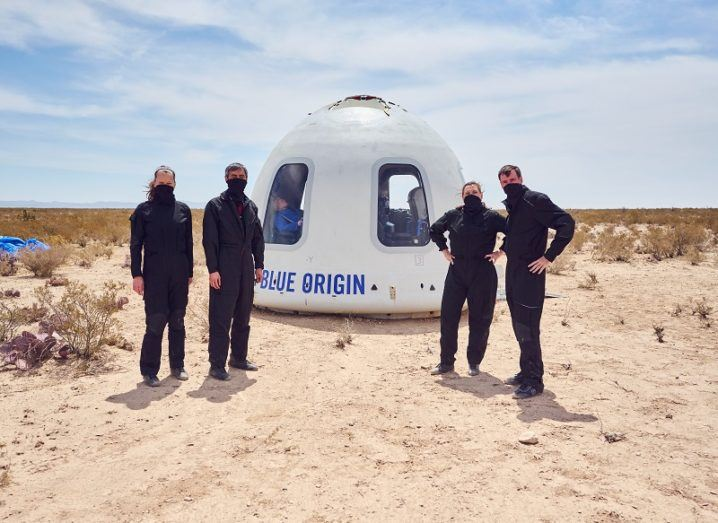 Four people stand in a desert beside a pod that says 'Blue Origin'.