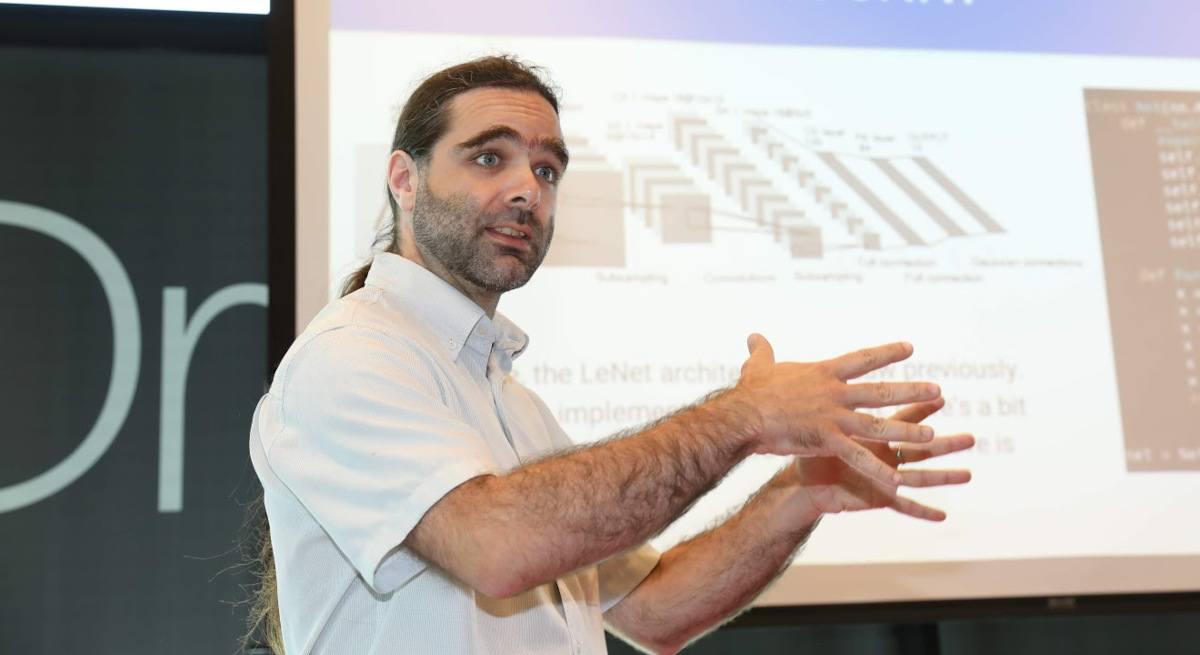 Le Dr Bruno Voisin de l'ICHEC présente la recherche à un public.