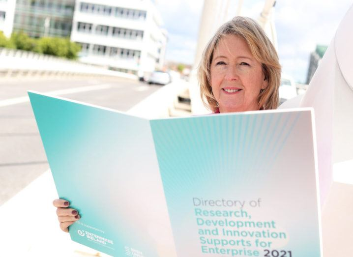 Alison Campbell of KTI stands on a bridge in Dublin city centre holding a large cardboard cutout of the new directory.