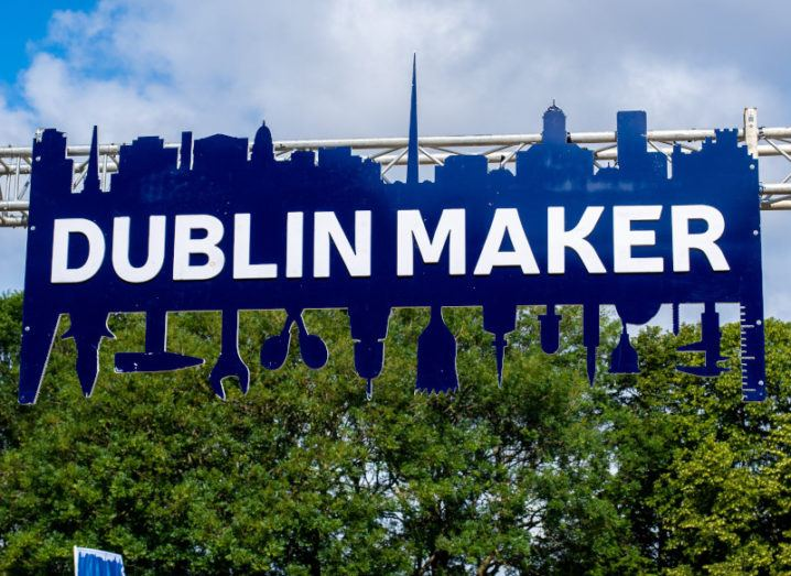 A large Dublin Maker sign suspended on a metal structure in Merrion Square park on a sunny day.