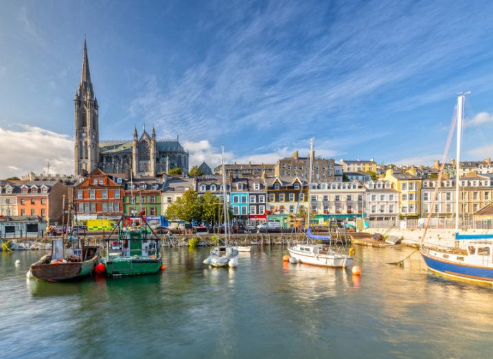 A picturesque photo of Cobh harbour, with several small boats in the water in front of colourful houses and a cathedral, highlighting tourism.