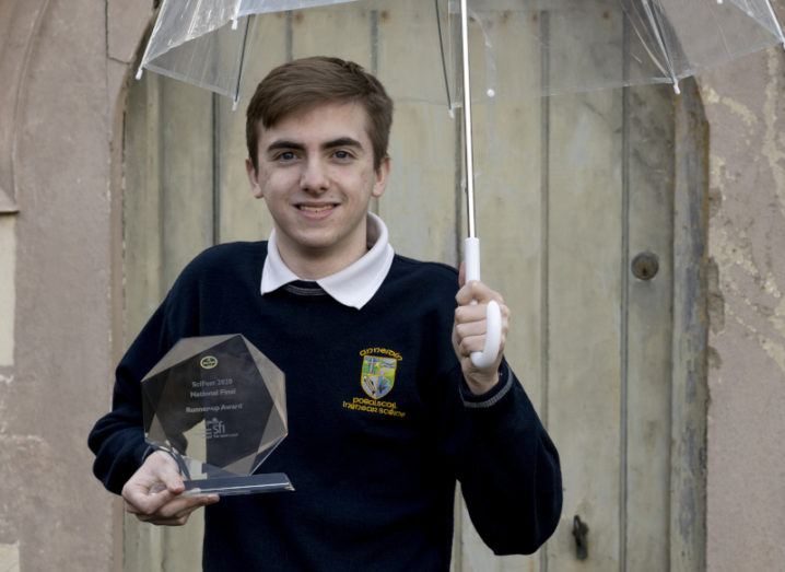 Conor Casey is standing outside holding an umbrella and his ISEF award while wearing his school uniform.