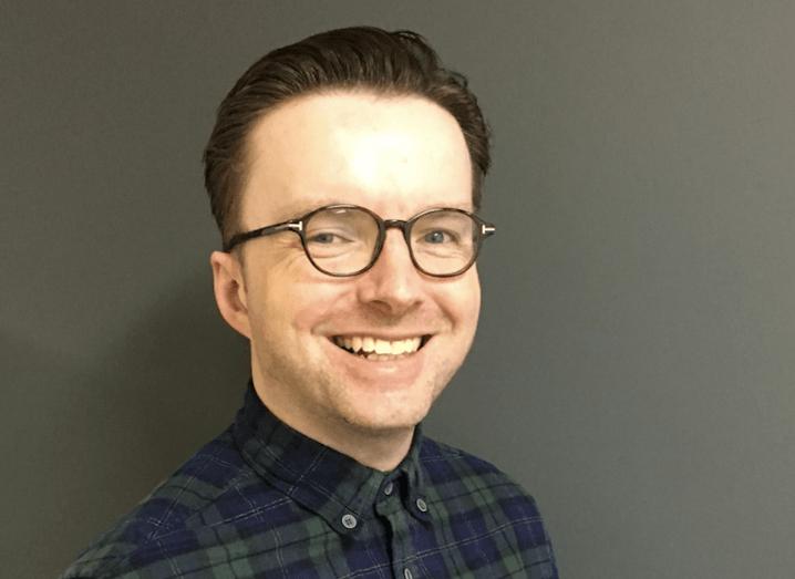 A headshot of David Savage, smiling at the camera against a dark grey wall.