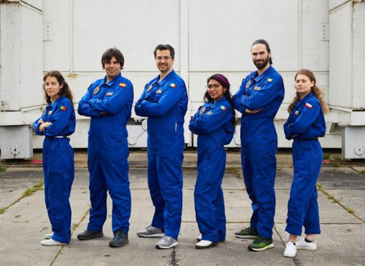 Six people in blue jumpsuits stand in a line.