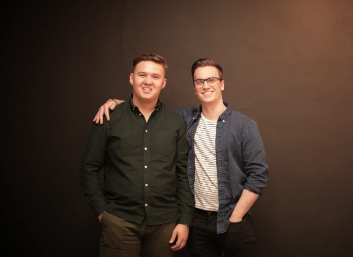 One young man has his arm around another. They are smiling standing in front of a dark wall lit from the right-hand side.