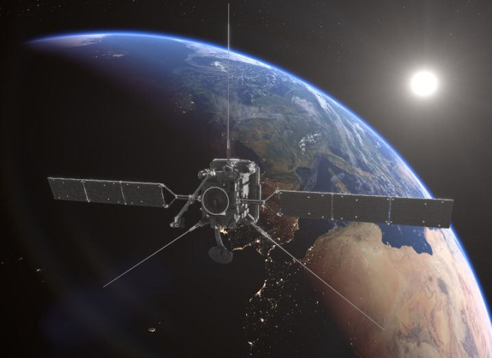A satellite floats in space in front of Earth.