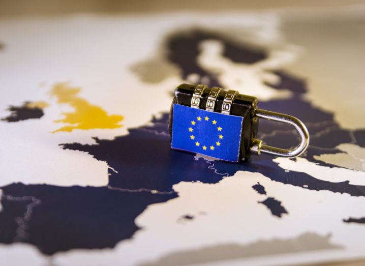 A small black padlock lies on its side on a map of Europe with a picture of the EU flag on the side of the lock.
